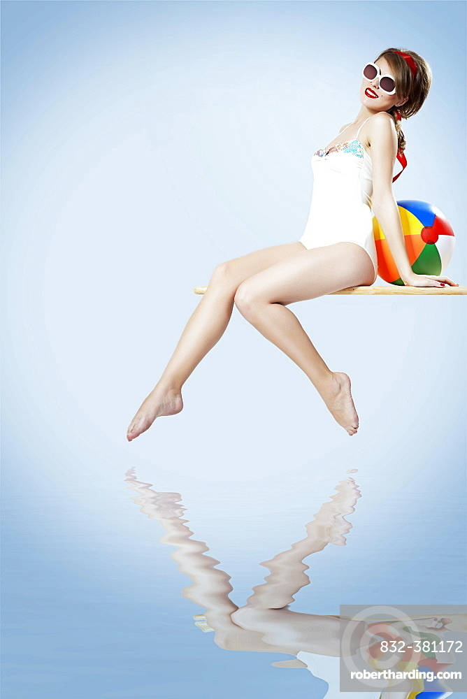 Young woman in a bright swimsuit and sunglasses sitting on a diving board, behind her a beach ball, pin-up