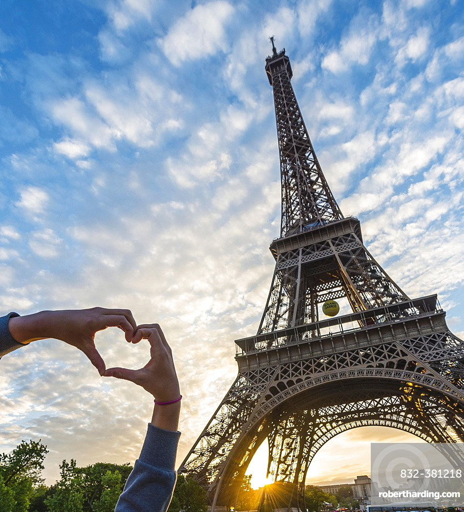 Hands forming heart, sunset behind Eiffel Tower, Champ de Mars, Paris, Ile-de-France, France, Europe