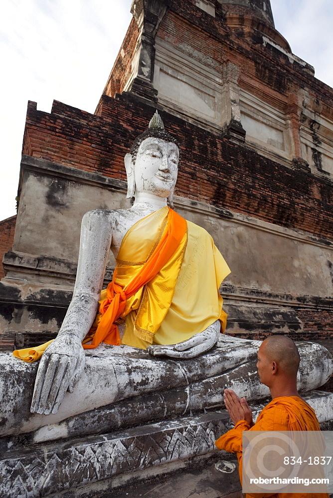 Monk in front of Buddha statue at Wat Yai Chai Mongkhon, Ayutthaya Historical Park, UNESCO World Heritage Site, Ayutthaya, Thailand, Southeast Asia, Asia