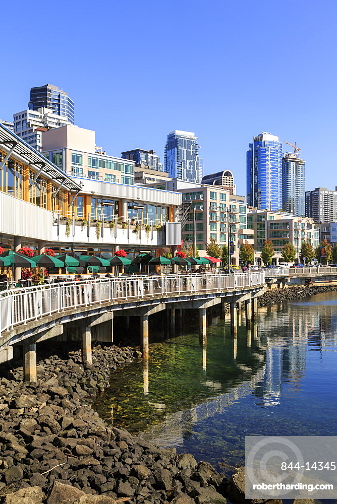Seattle Skyline and restaurants on sunny day in Bell Harbor Marina. Seattle, Washington, USA, North America