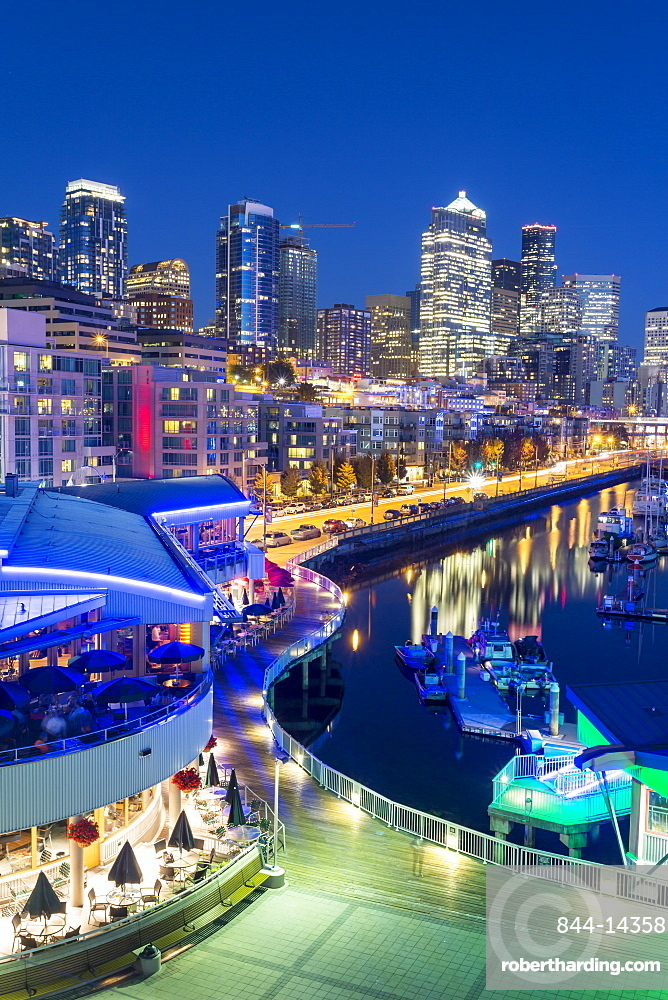 Elevated view of Seattle Skyline and restaurants in Bell Harbour Marina at dusk, Belltown District. Seattle, Washington, USA, North America
