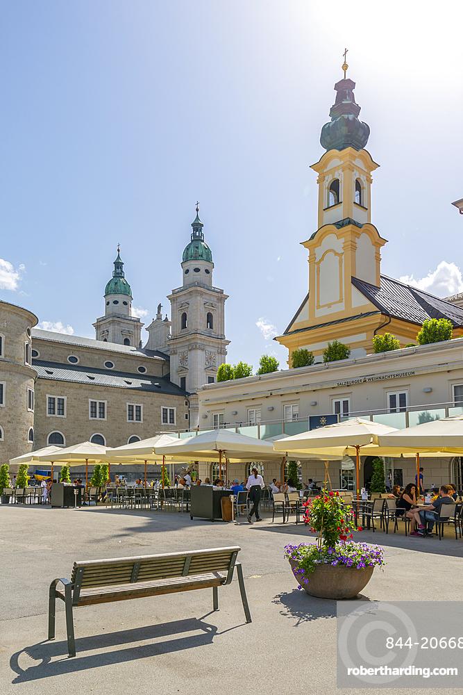 View of St. Michaelskirche and Salzburg Cathedral in Residenzplatz, Salzburg, Austria, Europe