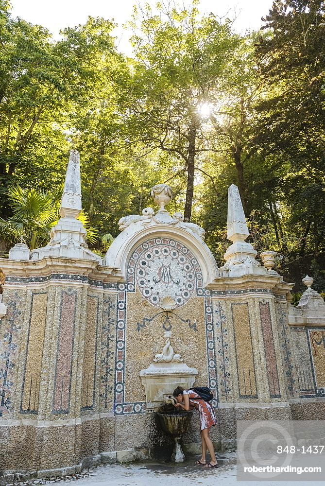 Woman using water fountain, Quinta da Regaleira, Sintra, Portugal, Europe