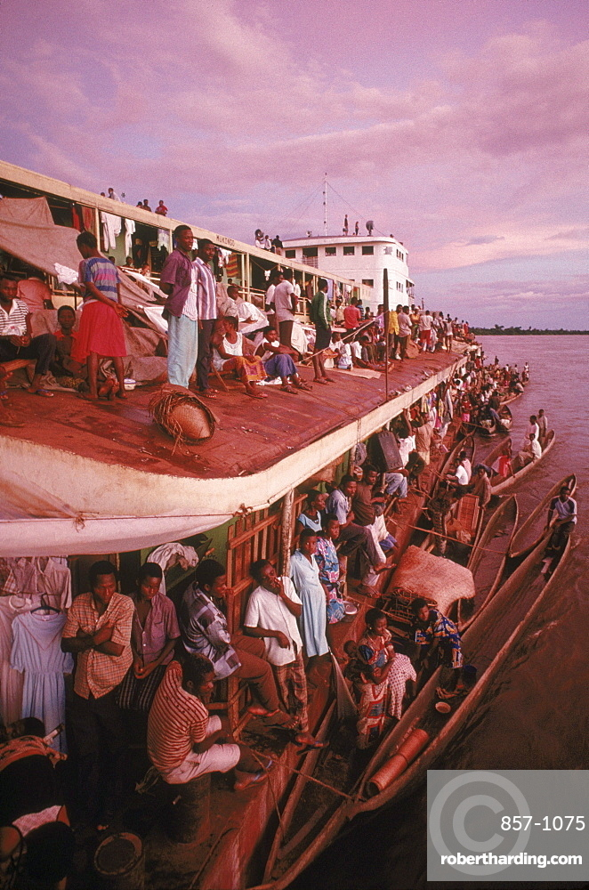 View of one of the crowded barges and the dugout canoes or pirogues which the fishermen and hunters who live along the Congo River use to bring bush meat to the boat to trade for salt, sugar and other goods.