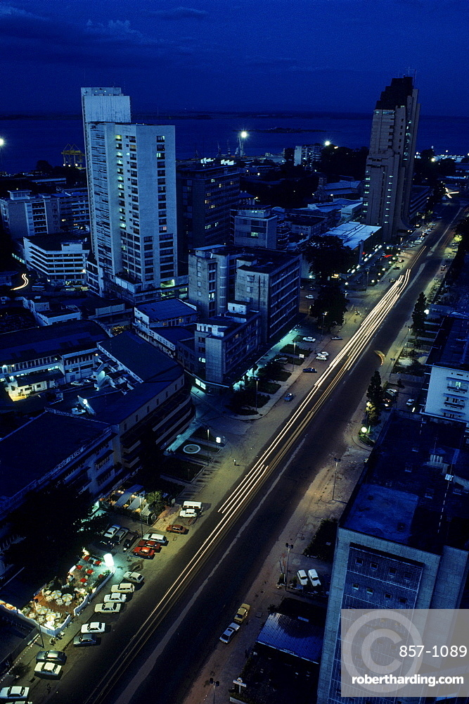 Scene of downtown Kinshasa at dusk showing the main street, the 20th Juin, cutting through the city.