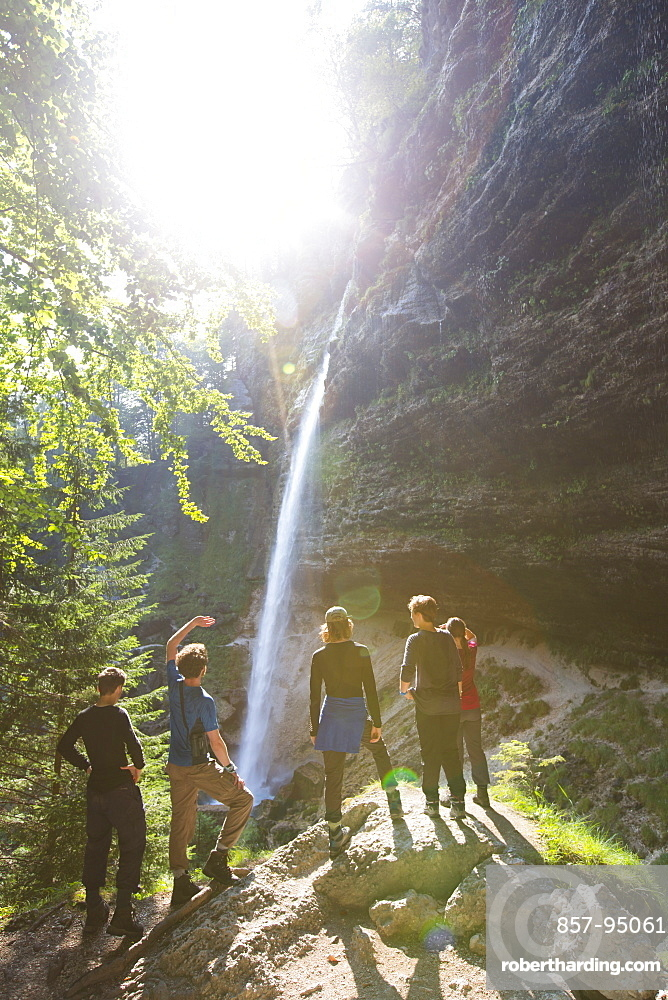 Group of young people standing at foot of Pericnik waterfall in alpine Vrata valley near Mojstrana in Triglav National Park, Slovenia