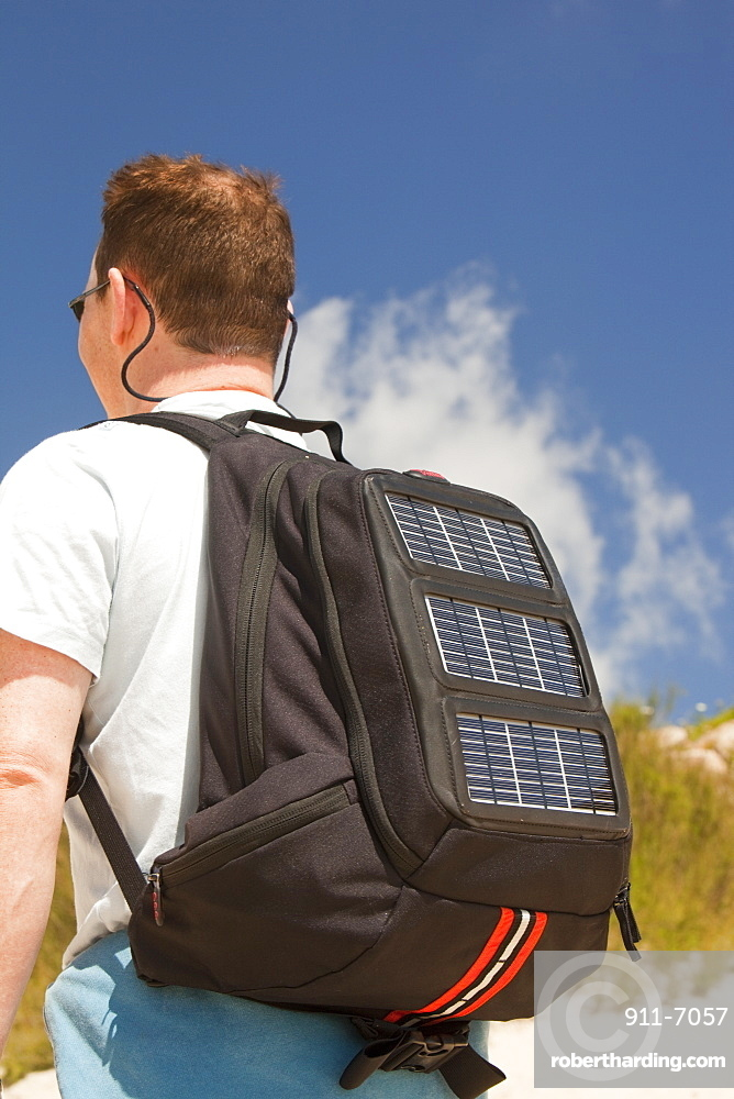 A man carrying a solar backpack, the solar panels can be used for recharging mobile phones and other electrical devices