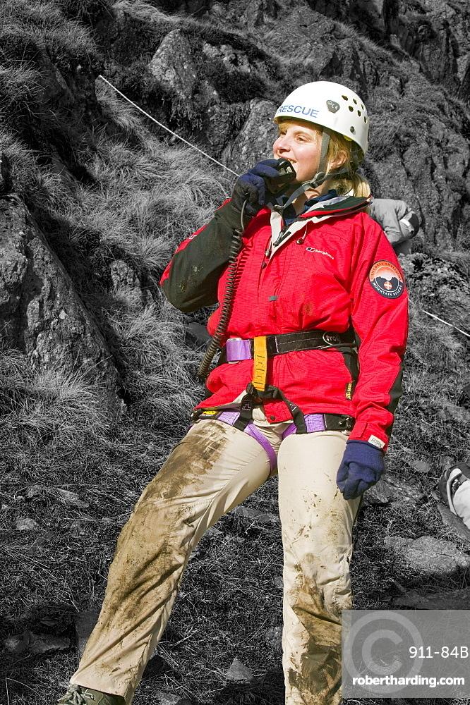 A female member of a mountain rescue team on the radio, Lake District, Cumbria, England, United Kingdom, Europe