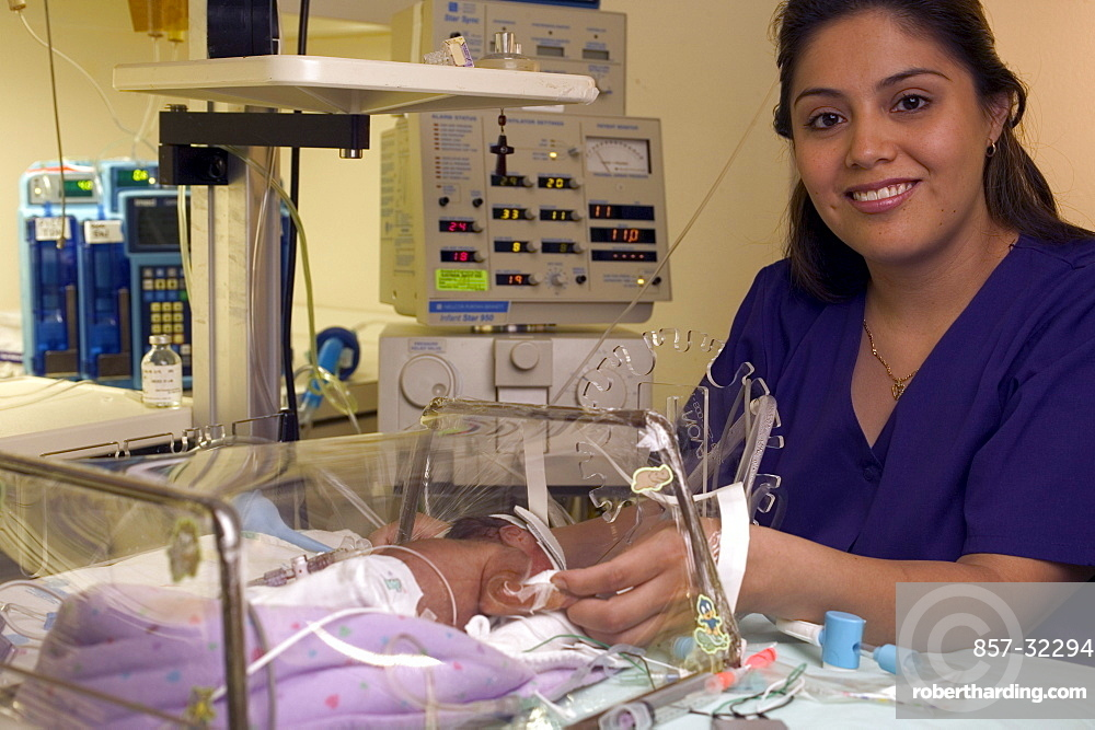 A mother stands next to the incubator in which her premature child rests.