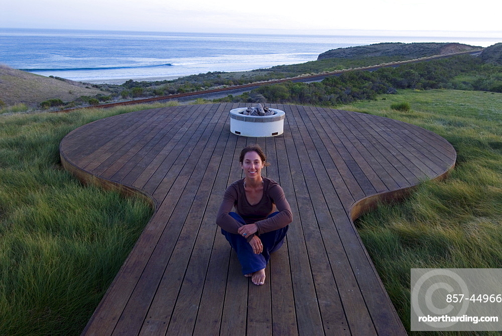 A yong woman watches the sunset from a deck overlooking the Pacific Ocean at Hollister Ranch, California.