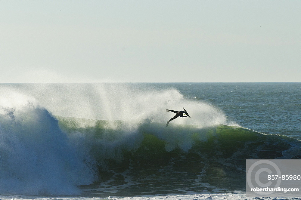Bodyboarder does this aerial on a massive wave, backlite by sunset, at NAzare Special Edition contest, held in Nazare Portugal.