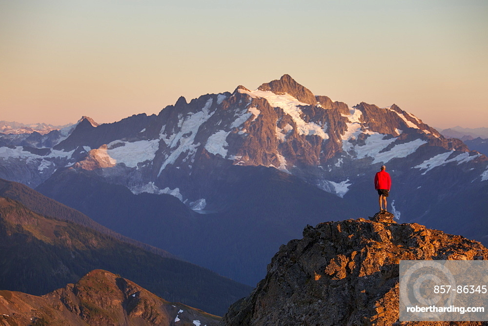 A hiker stands on a rocky ridge in the North Cascade Mountains with Mount Shuksan in the background, North Cascades National Park, Washington, United States