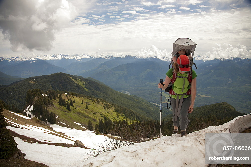 A woman carrying an infant hiking in the mountains. hiking in the mountains, Cascade Mountains, , Washington