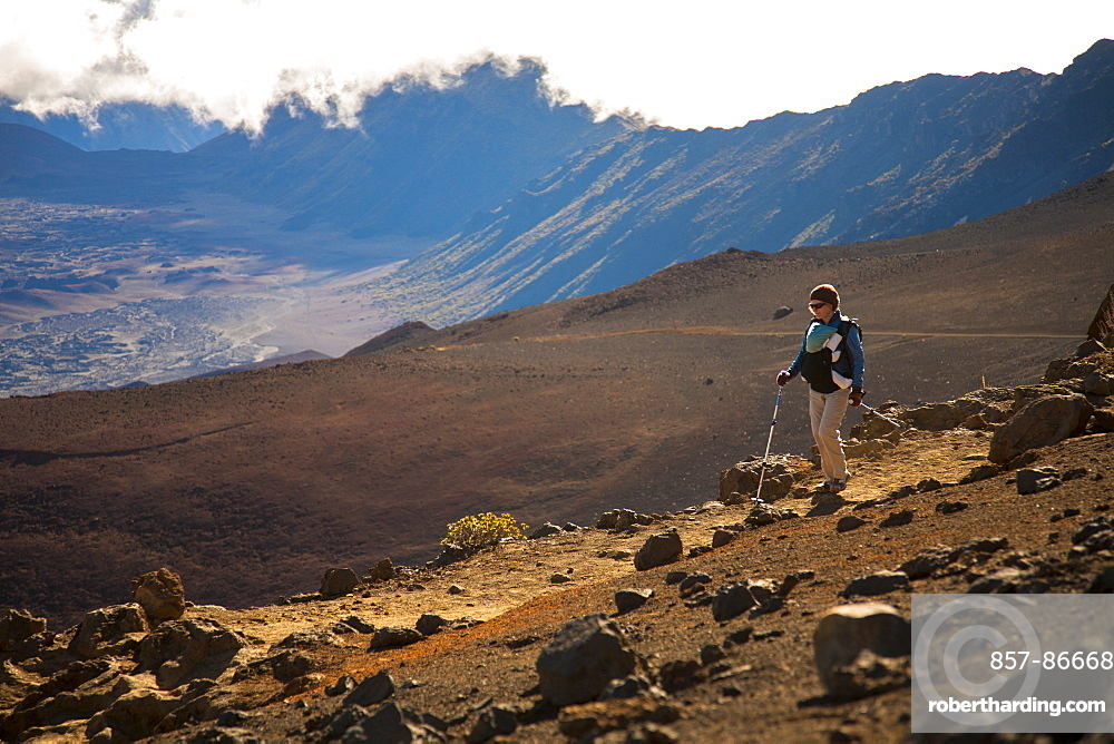 A woman in her thirties carrying an infant hikes in the high-elevation volcanic Haleakala crater, Maui, Hawaii, United States of America