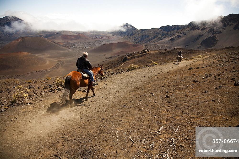Two men on horseback ride into Haleakala crater, Maui, Hawaii, United States of America