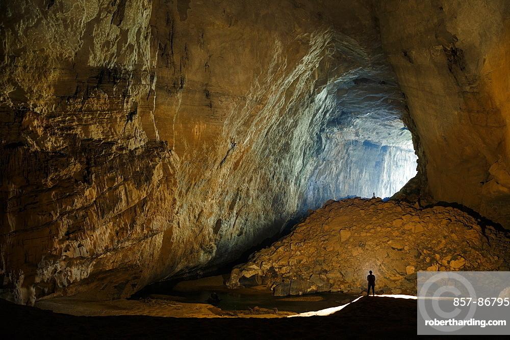 Cave explorers illuminate a large passage in Hang En, Phong Nha Ke Bang National Park, Vietnam.