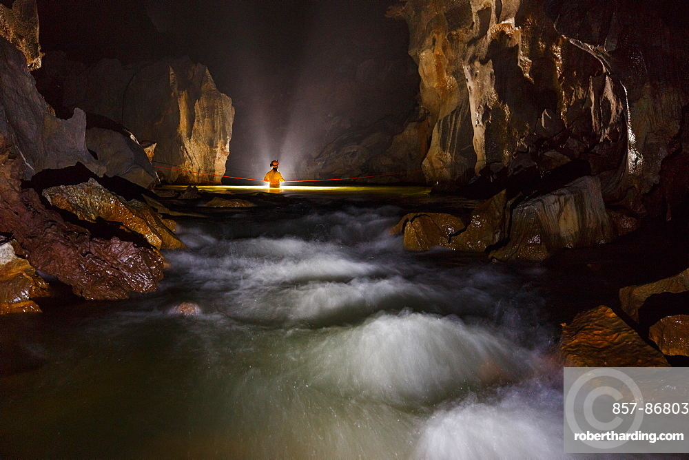 A cave explorer crosses a fast flowing river in Hang Son Doong, Vietnam