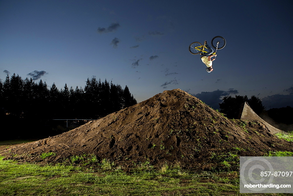 A young man performs a backflip jump in his backyard dirt track near the city of Toluca, Mexico