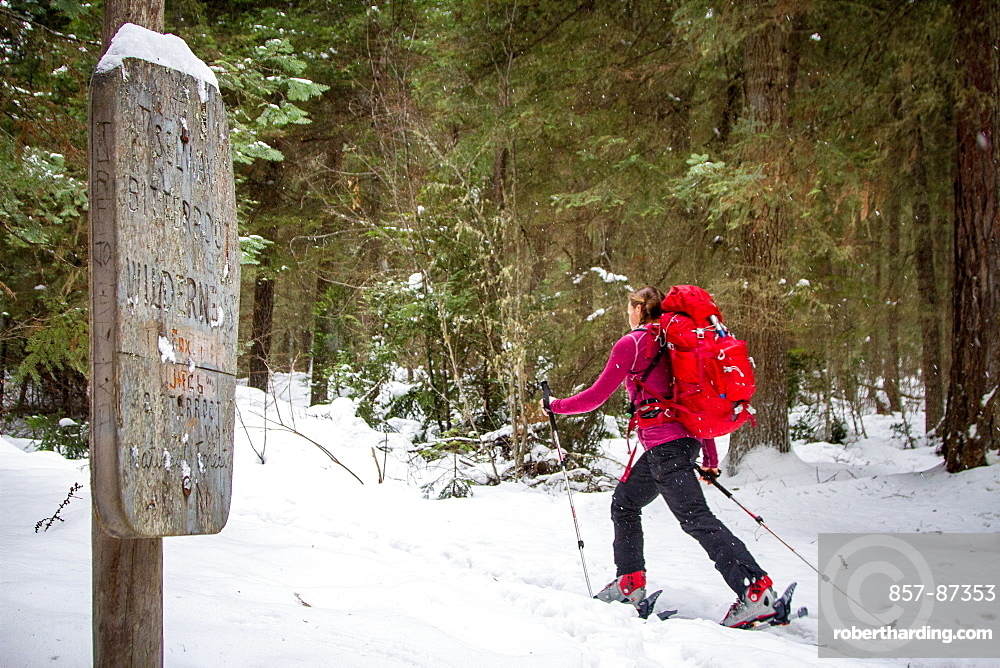 A woman backcountry skier skis by a sign marking the beginning of the Selway-Bitterroot Wilderness in Montana.