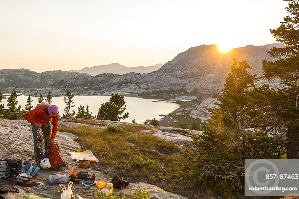 A woman packing up camp to head home after a week rock climbing in Titcomb Basin, Wind River Range, Bridger Teton National Forest,  Pinedale, Wyoming.