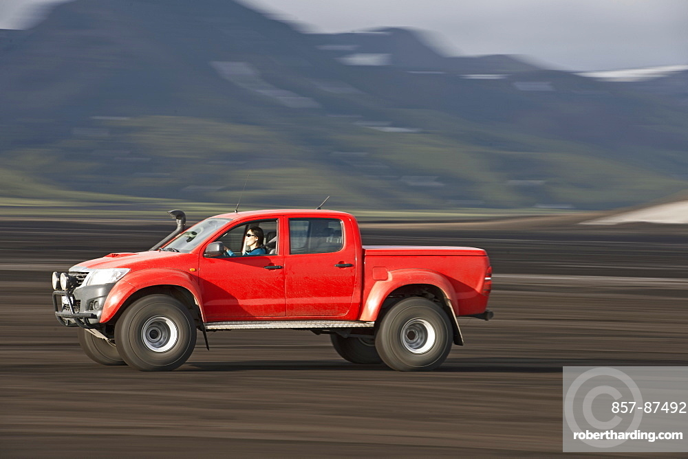 Woman driving customized pick up truck on Maelifellssandur area on the Icelandic highlands