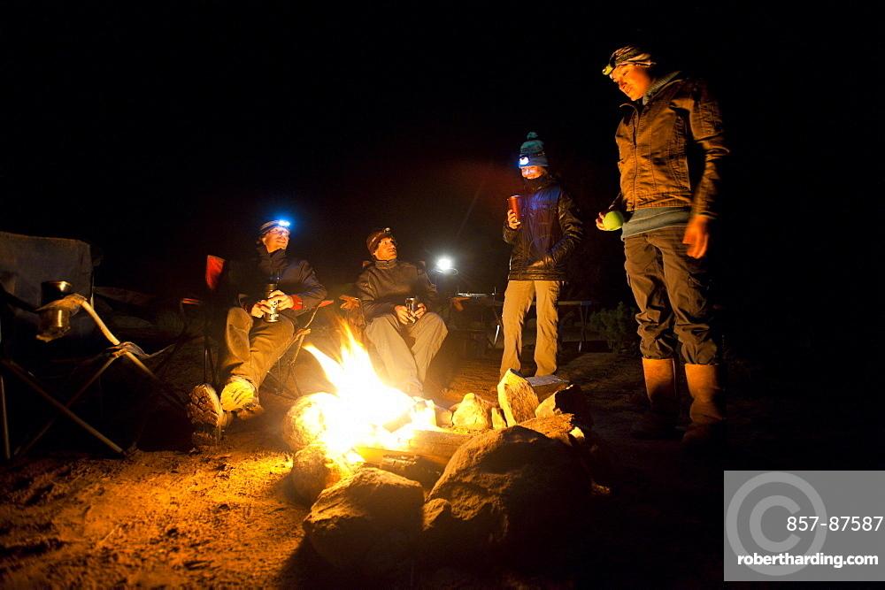 Dave Steiner, Ephraim Learned, Maria Hidalgo, and Chessa Jones sit around a campfire in Moab, Utah.