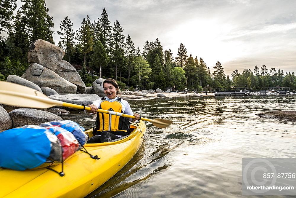 Woman laughing while paddling a kayak on the lake.