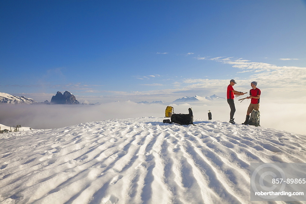 Two climbers pack up their tent after camping on the snow in the mountains of British Columbia, Canada.