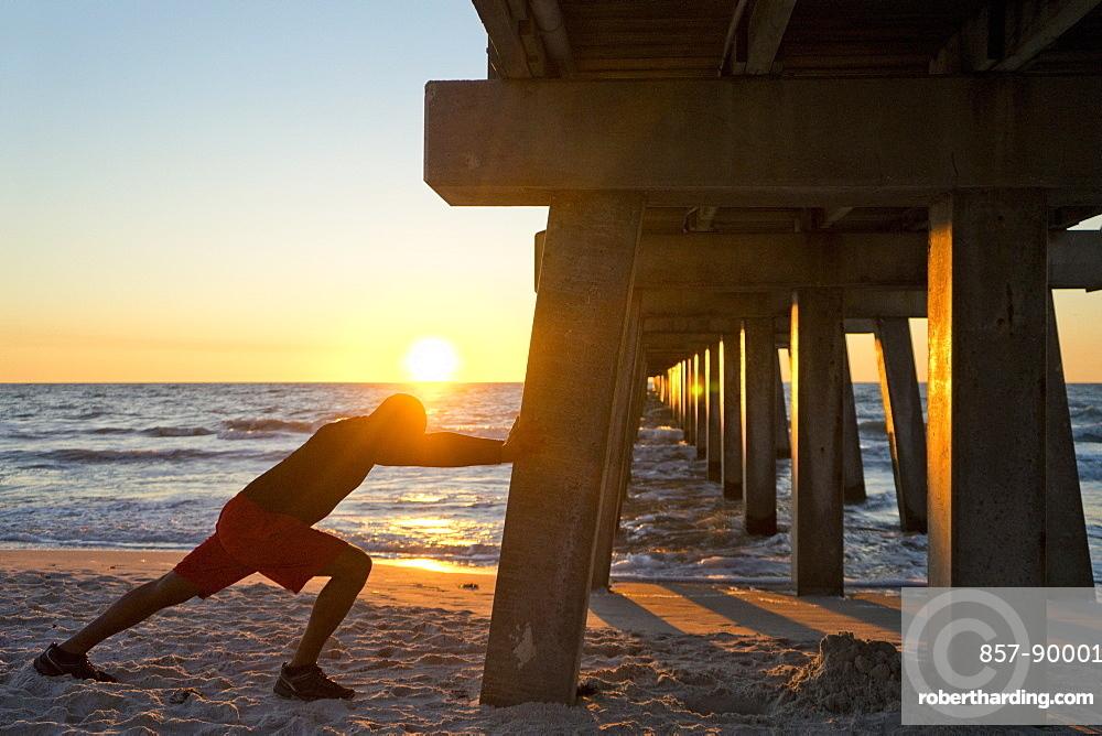 Man stretching, using a pier pillar on the beach at sunset
