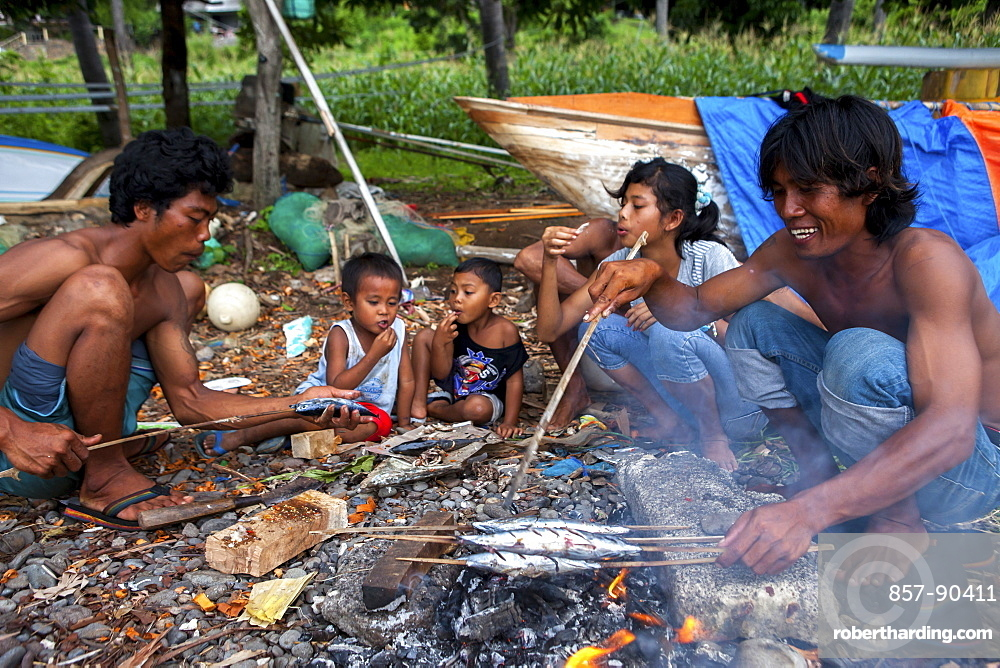 A fisherman?s family eats after cooking the fish they caught in the town of Amed in Bali, Indonesia.