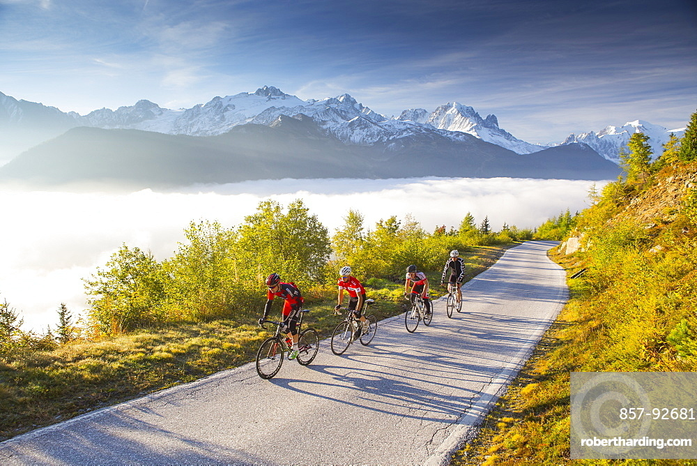 Four road bikers on a winding mountain road on their way to the Emosson reservoir lake in the Alps on the border of France and Switzerland. It is an early morning training session of the local cyclists. The sun is rising, clouds are in the valley, and in the background the mountain peaks of Chamonix are visible, including Mont Blanc, the highest mountain of the Alps. This climb will be stage 17 of the 2016 Tour de France on July 20th 2016. Depart is in Bern and the finish near the Emosson reservoir at 1960 meters height.