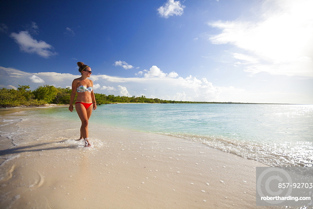 A young attractive woman walks on the beach in Cayo Coco, Cuba.