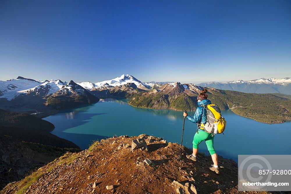 A backpacker reaches the summit of Panorama Ridge, overlooking Garibaldi Lake in Garibaldi Provincial Park, British Columbia, Canada.