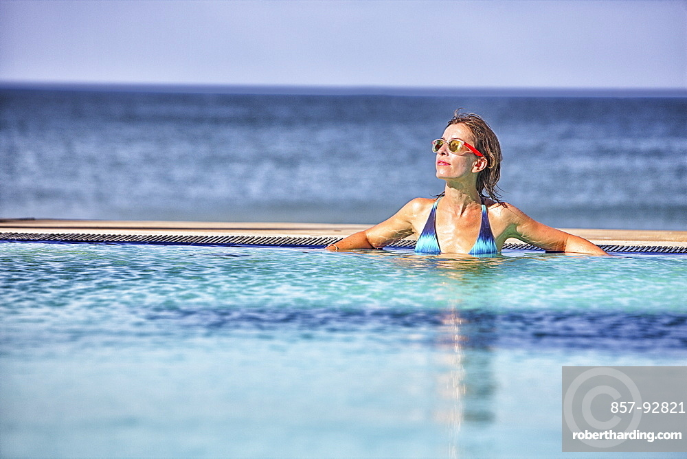 Woman sunbathing by a pool in Nilaveli. Sri Lanka