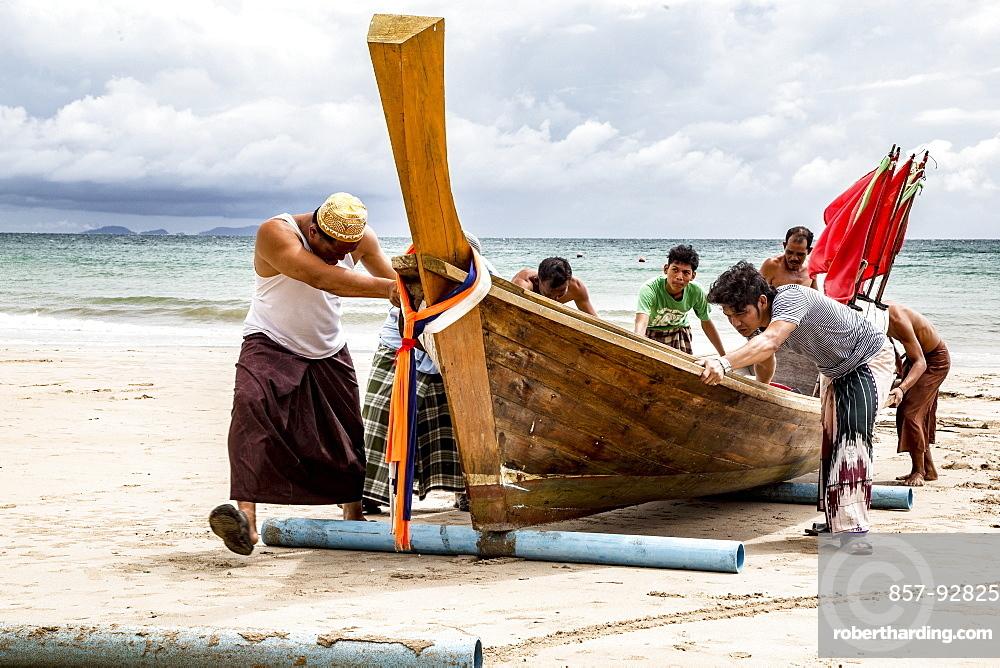 Fishermen on Koh Lanta Island in Thailand push Boat to Shore