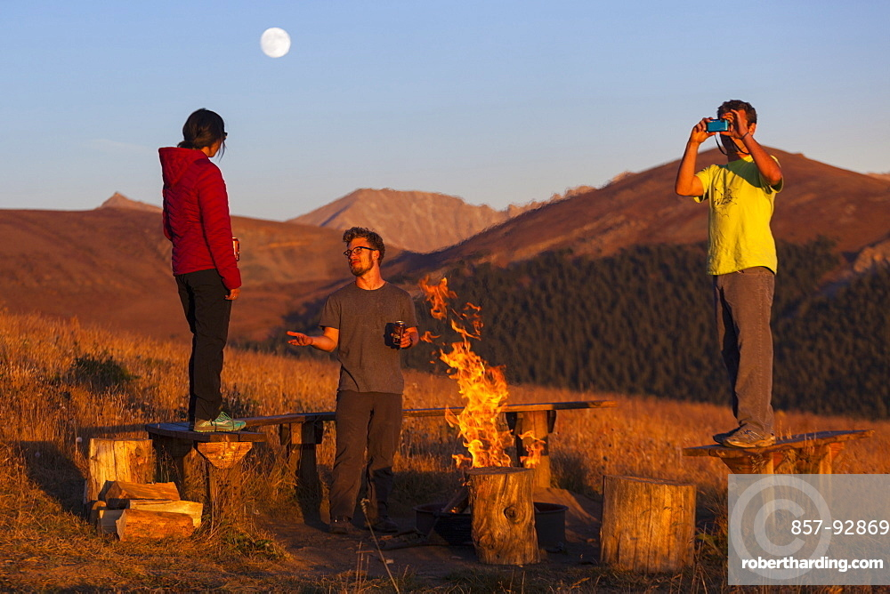 Friends hang out by the campfire outside the Jackal Hut, White River National Forest, Colorado.