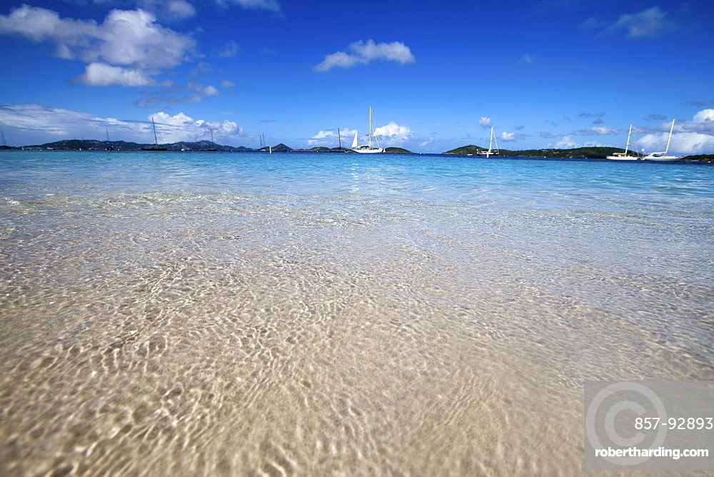 Crystal clear Caribbean water and bright blue skies provide a perfect scene with sailboats moored off of Honeymoon Beach, St. John, USVI.
