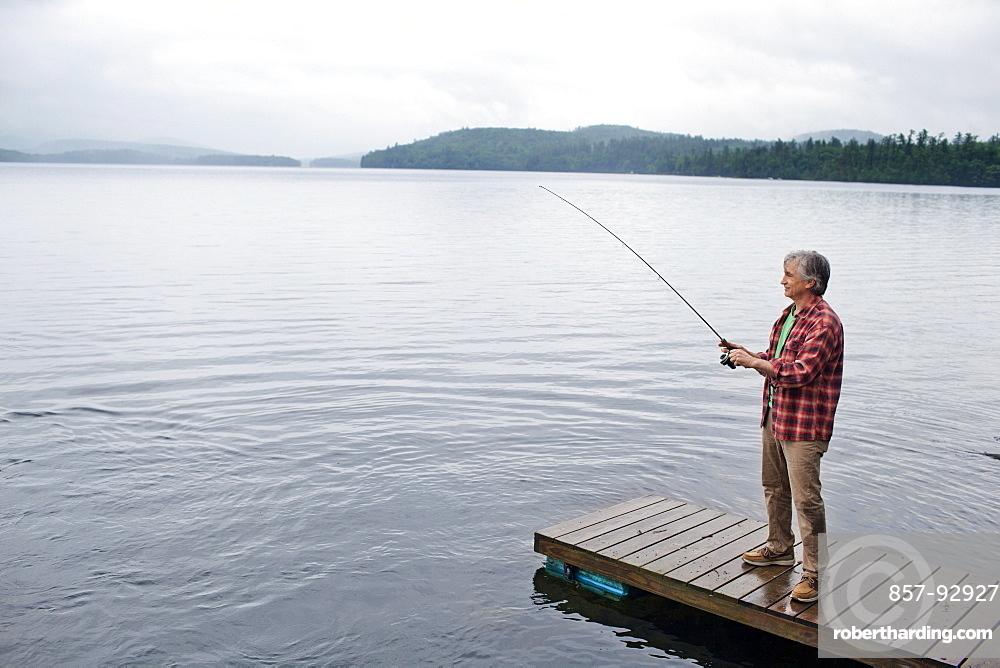 Senior man fishing off dock at Kezar Lake