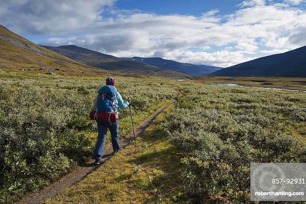 Hiker on trail through Tjäktjavagge south of Singi hut, Kungsleden trail, Lapland, Sweden