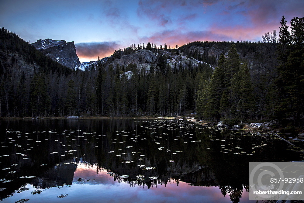 Reflection of the mountains and Hallet Peak on a lake at sunset in Rocky Mountain National Park, Colorado