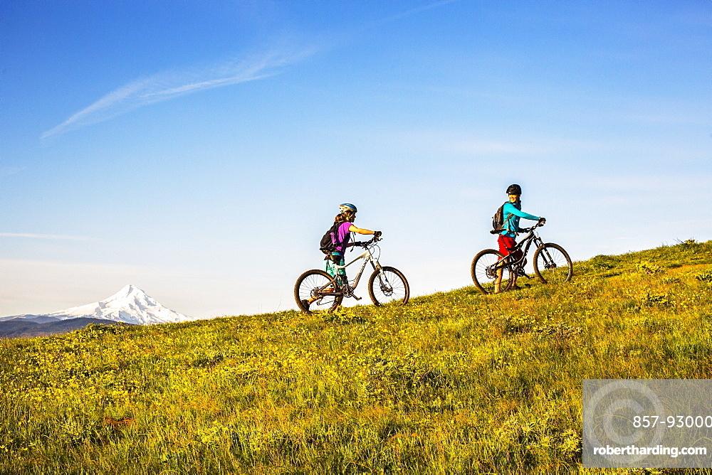 Two young women push mountain bikes up a single-track trail through an open meadow.