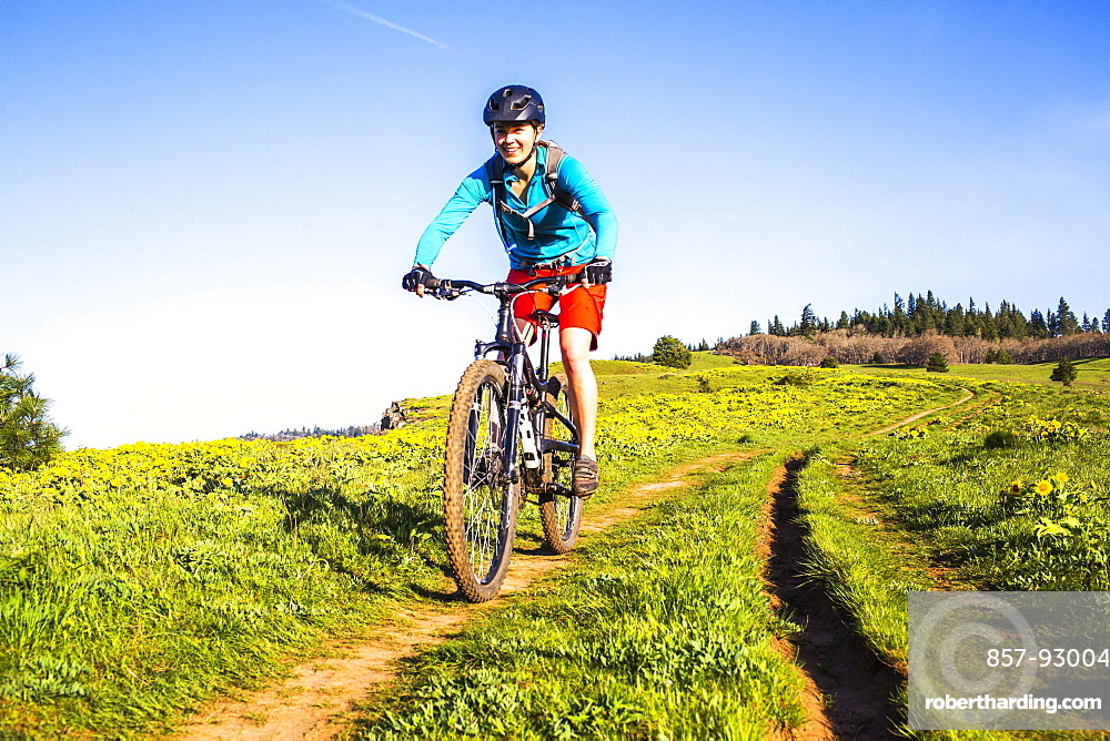 A young woman facing camera rides a mountain bikes down a single-track trail through a meadow.
