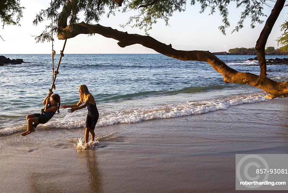 Children play with a rope swing on Waialea beach on the Big Island of Hawaii.