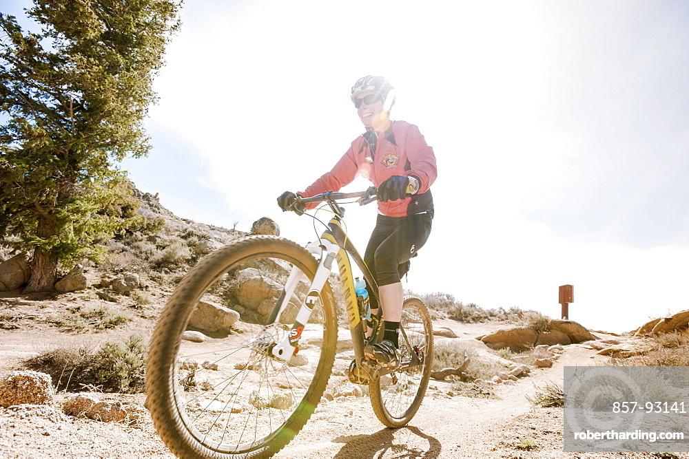 Smiling Woman Mountain Biking On Rocky Landscape In Gunnison