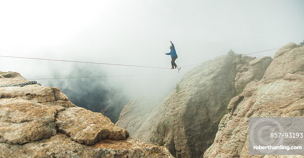 Man Walking On Slackline In Fog Over A Canyon