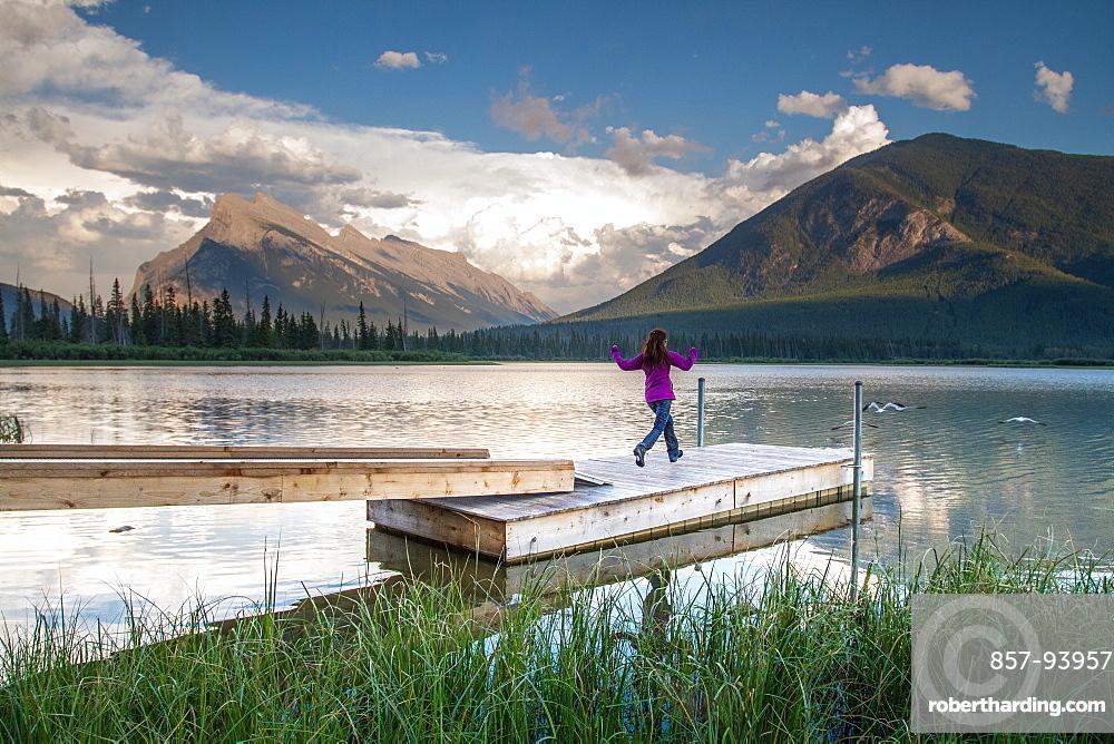 Young girl runs along wharf at mountain lake