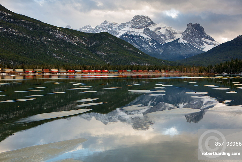 Mountains and train relected in lake