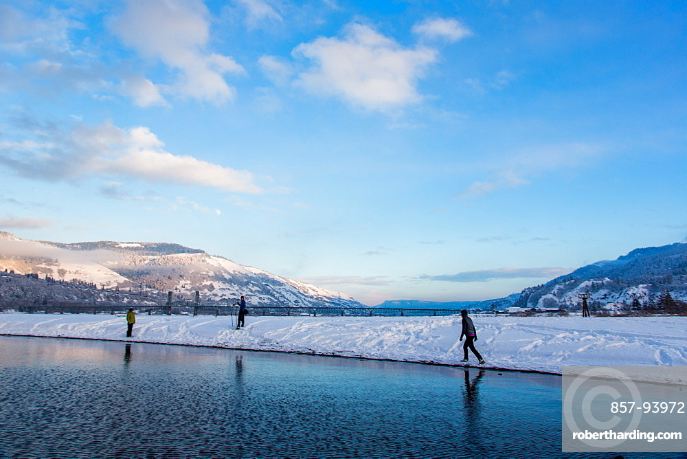 People walking along snow covered shore of Columbia River on sunny evening
