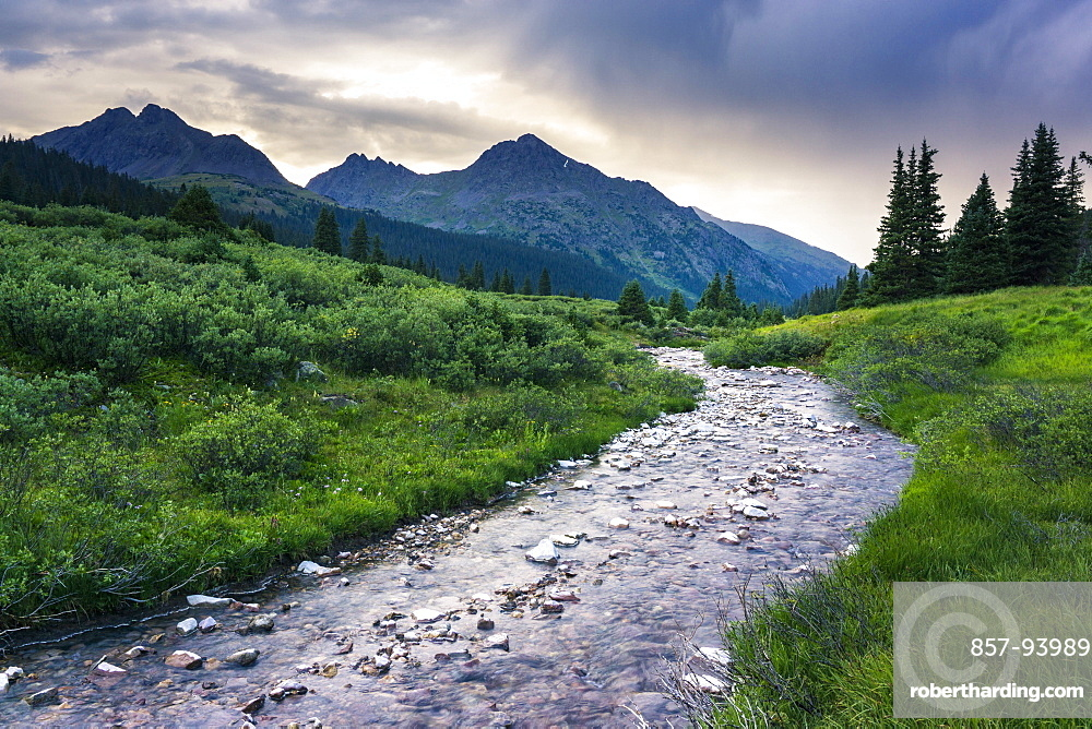 Colorado mountain scene with a river and mountains after a thunderstorm during sunset