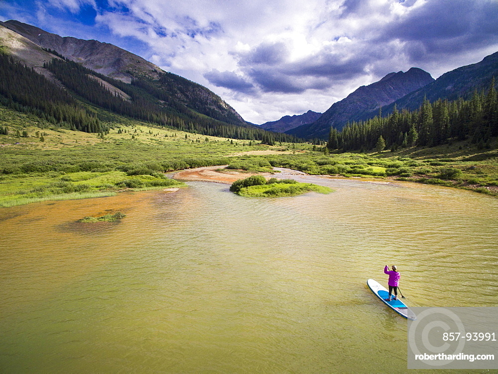 A female paddleboarding on a high alpine lake before a thunderstorm